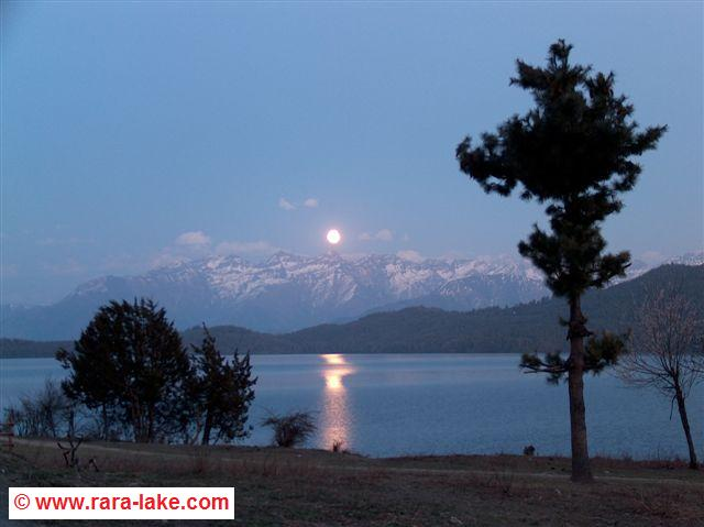 full moon rising above the lake